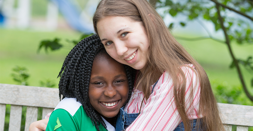 Two girls sit and smile at the camera. Promotional photo for summer 2017 Home's Grown Kids Newsletter.